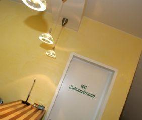 Cooperated Design auch beim Empfang. Die Farben Gelb, Grün und Silber finden Sie in der gesamten Ordination.